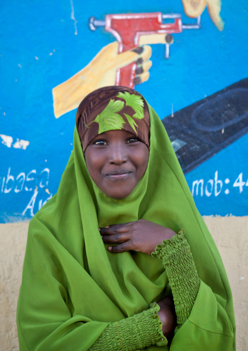 Portrait of a young teenage girl wearing a green hijab in front of a painted wall, Boorama, Somaliland