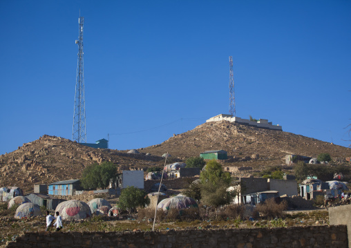 Antennas on top of hills and slum huts village down in a dry area, Boorama, Somaliland