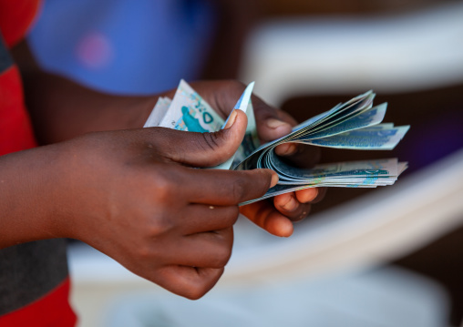 A man is counting schillings notes, Awdal region, Zeila, Somaliland