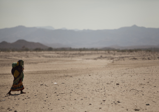 A woman is walking in a desert rocky place with  mountains in the background, Hargeisa, Somaliland