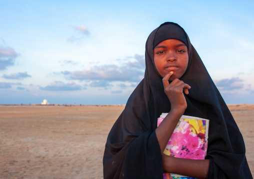 Portrait of a somal girl in black veil with a school book, Awdal region, Zeila, Somaliland