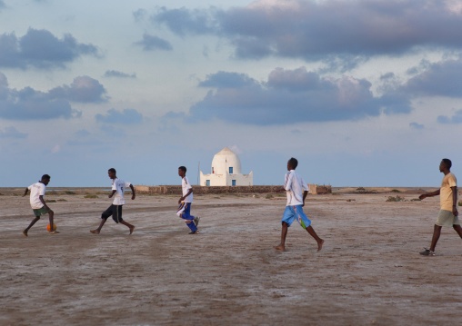 Young boys playing football with mausoleum in background, Zeila, Somaliland