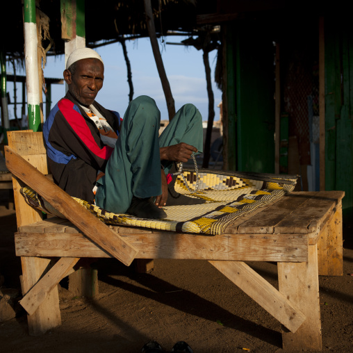 Mature man sat outdoors on wooden couch, Zeila, Somaliland