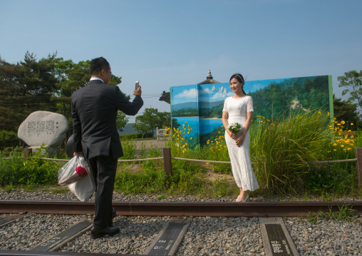 North korean defector joseph park taking a picture of his south korean fiancee juyeon on the north and south korea border, Sudogwon, Paju, South korea