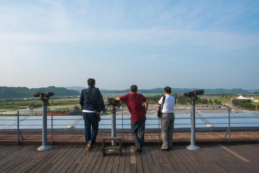 South korean men looking over the north and south korea border at the jsa, Sudogwon, Paju, South korea