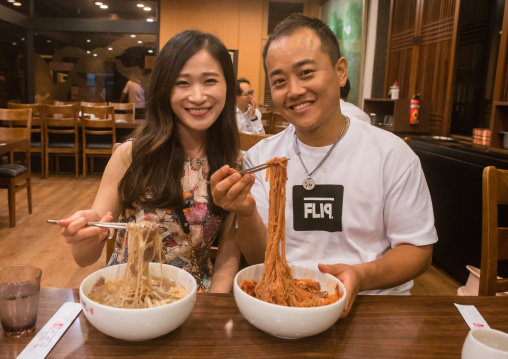 North korean defector joseph park with his south korean fiancee called juyeon eating cold noodles, National capital area, Seoul, South korea