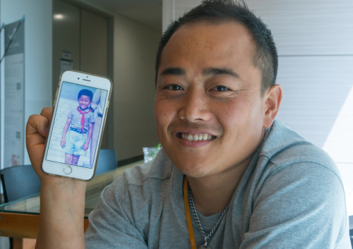North korean defector joseph park in yovel cafe showing a picture of himself taken in north korea, National capital area, Seoul, South korea