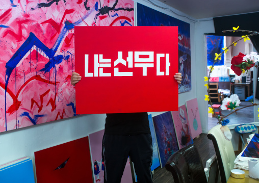 Sun mu artist hiding behind one of his painting, National capital area, Seoul, South korea