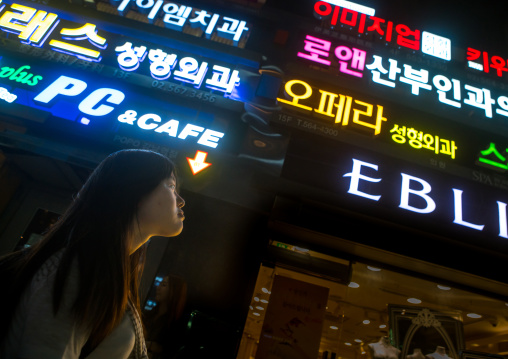 North korean teen defector in front of neon lights in the street, National capital area, Seoul, South korea