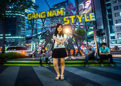 North korean teen defector in front of a gangnam style logo dancing like psy, National capital area, Seoul, South korea