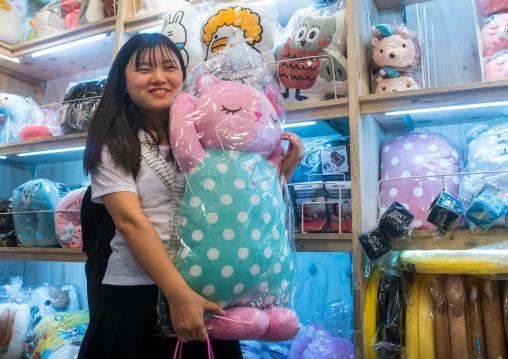 North korean teen defector buying a funny pillow, National capital area, Seoul, South korea