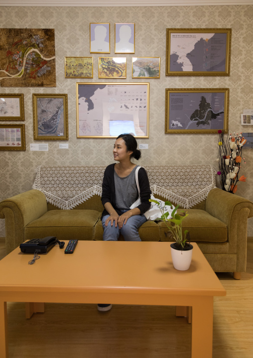 South Korean visitor sit below the portraits of the dear leaders with the pictures removed during the exhibition Pyongyang sallim showing a north Korean apartment replica, National Capital Ar