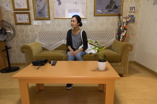South Korean visitor sit on a sofa during the exhibition Pyongyang sallim at architecture biennale showing a north Korean apartment replica, National Capital Area, Seoul, South Korea