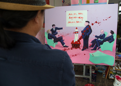North Korean artist Sun Mu in front of a painting with Donald Trump and Kim Jong Un, National Capital Area, Seoul, South Korea