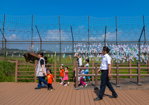 South Korean family passing in front of messages of peace and unity written on ribbons left on fence at DMZ, North Hwanghae Province, Panmunjom, South Korea