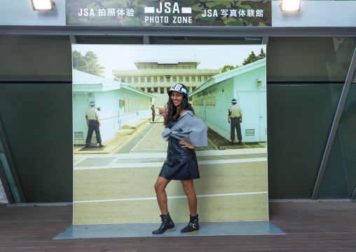 Tourist posing in front of a giant picture of the DMZ border, North Hwanghae Province, Panmunjom, South Korea