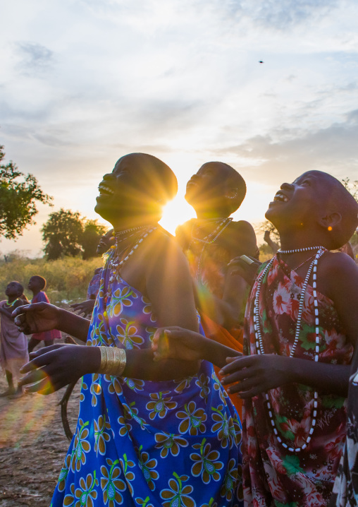Toposa tribe women in traditional clothing looking at the sky, Namorunyang State, Kapoeta, South Sudan
