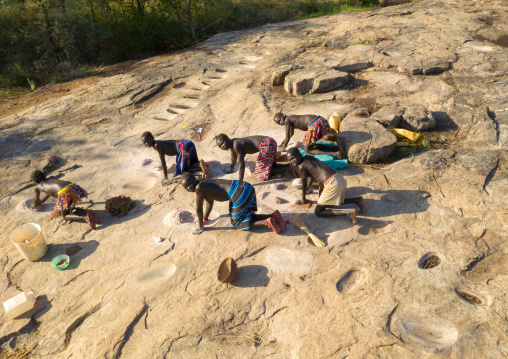 Larim tribe women grinding sorghum grains in holes in a rock, Boya Mountains, Imatong, South Sudan