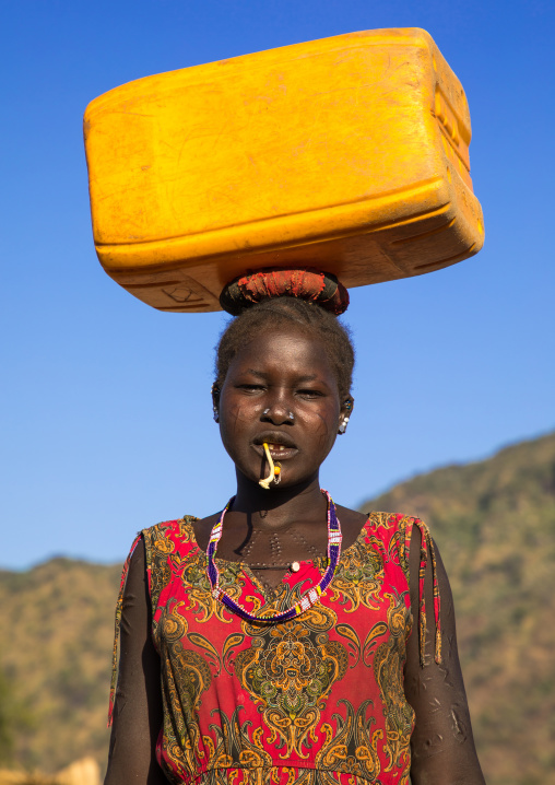 Portrait of a Larim tribe woman carrying a jerrycan of water on the head, Boya Mountains, Imatong, South Sudan