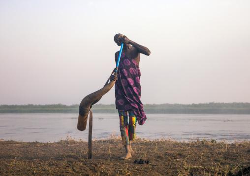 Mundari tribe man blowing in a cow horn, Central Equatoria, Terekeka, South Sudan