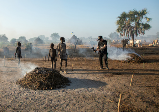 Tourist filming Mundari tribe boy taking care of the bonfires made with dried cow dungs, Central Equatoria, Terekeka, South Sudan