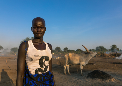 Mundari tribe women with her long horns cows in a camp, Central Equatoria, Terekeka, South Sudan