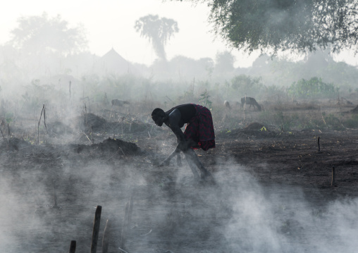 Mundari tribe woman taking care of a bonfire made with dried cow dungs to repel mosquitoes, Central Equatoria, Terekeka, South Sudan