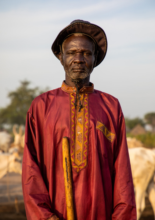 Portrait of a Mundari tribe man in traditional clothing with his cows, Central Equatoria, Terekeka, South Sudan