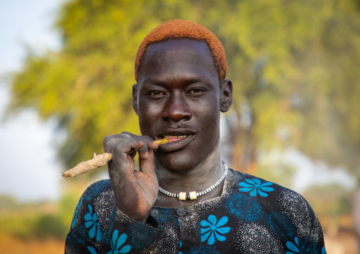 Portrait of a Mundari tribe man with hair dyed in orange with cow urine using a wooden toothbrush, Central Equatoria, Terekeka, South Sudan