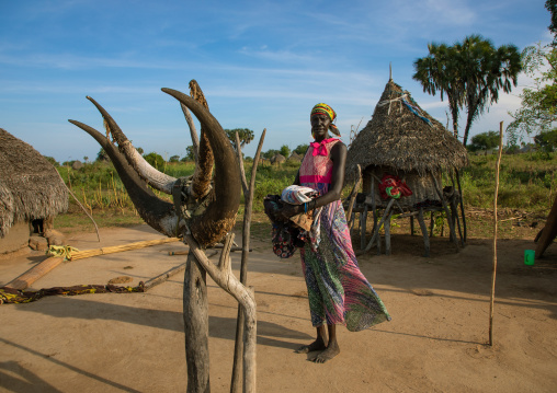 Mundari tribe woman standing in front of a totem made of cow horns, Central Equatoria, Terekeka, South Sudan