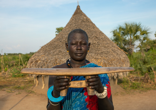 Mundari tribe woman showing a traditional wooden pillow, Central Equatoria, Terekeka, South Sudan