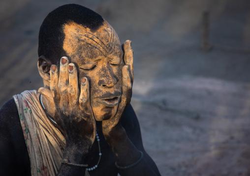 Mundari tribe man covering his body in ash to repel flies and mosquitoes, Central Equatoria, Terekeka, South Sudan