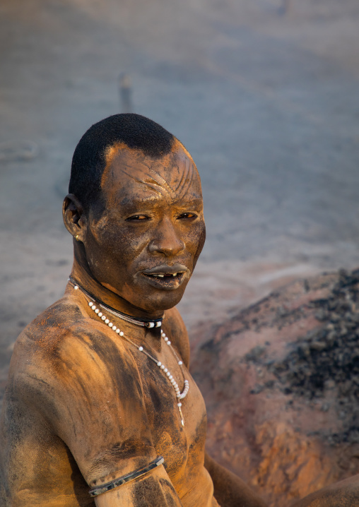 Mundari tribe man covering his body in ash to repel flies and mosquitoes, Central Equatoria, Terekeka, South Sudan