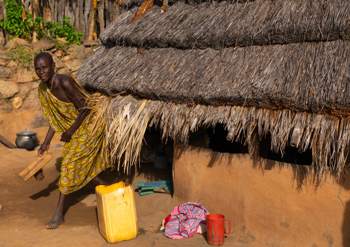 Lotuko tribe woman coming out from her thatched hut, Central Equatoria, Illeu, South Sudan