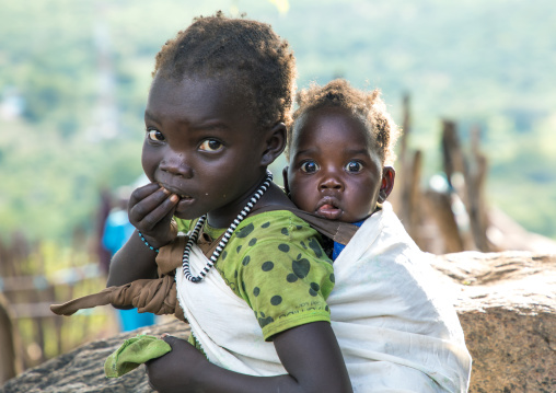Lotuko tribe girl carrying her sister on her back, Central Equatoria, Illeu, South Sudan