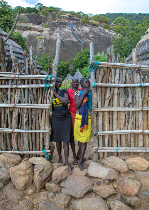 Lotuko tribe girls standing at the wooden gate of a house, Central Equatoria, Illeu, South Sudan