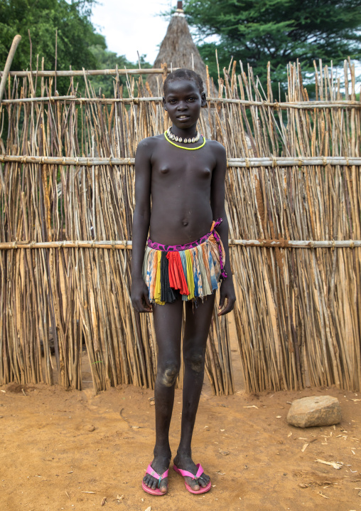 Larim tribe teenage girl in front of her traditional house, Boya Mountains, Imatong, South Sudan