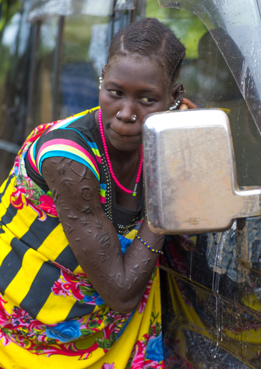 Larim tribe woman with scarifications on her arm looking at herself in a car mirror, Boya Mountains, Imatong, South Sudan