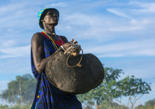 Mundari tribe woman carrying a huge bell while celebrating a wedding, Central Equatoria, Terekeka, South Sudan