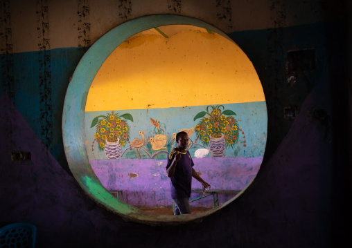 Sudanese man passing inside a circular window in a restaurant, Khartoum State, Khartoum, Sudan