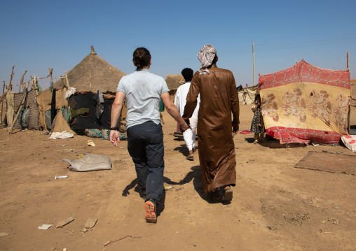 Rashaida man hand in hand with a tourist in a village, Kassala State, Kassala, Sudan