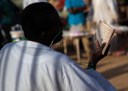 Sudanese man reading the quran during the friday sufi celebration at sheikh Hamad el Nil tomb, Khartoum State, Omdurman, Sudan
