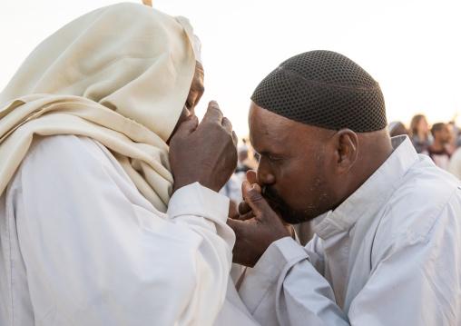 Men kissing hands during the friday sufi celebration at sheikh Hamad el Nil tomb, Khartoum State, Omdurman, Sudan