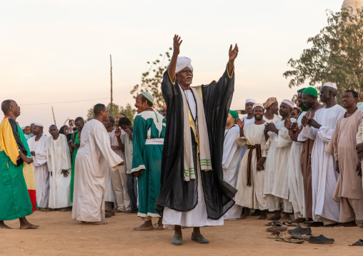 Man with arms raised leading the friday sufi celebration at sheikh Hamad el Nil tomb, Khartoum State, Omdurman, Sudan