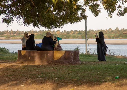Girl with digital tablet photographing friends in front of the river Nile, Northern State, Al-Khandaq, Sudan