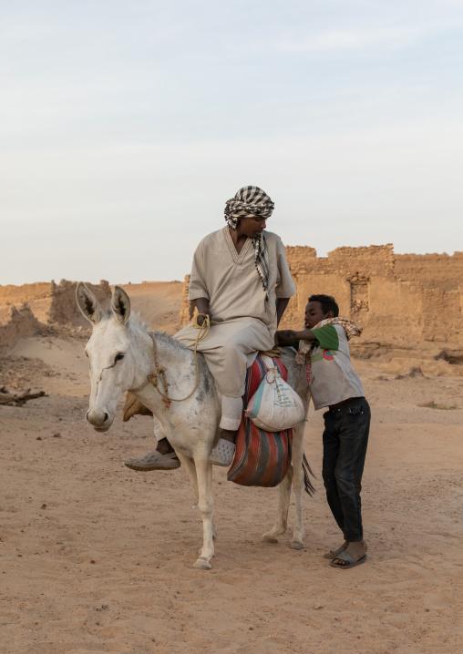 Sudanese men riding a donkey, Northern State, Al-Khandaq, Sudan
