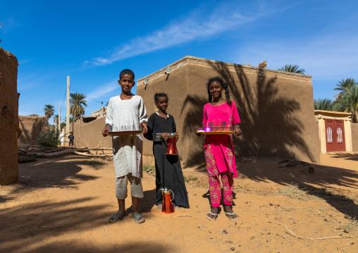 Sudanese children offering tea to visitors in a village, Northern State, Karima, Sudan