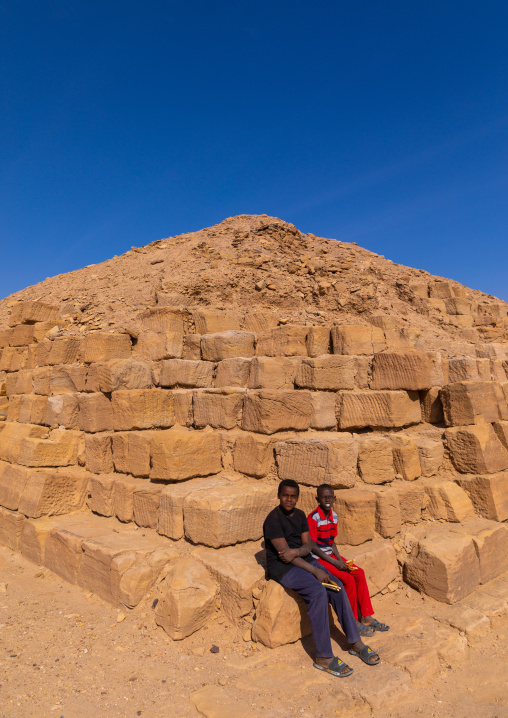 Sudanese children sit on a pyramid in the royal cemetery, Northern State, El-Kurru, Sudan