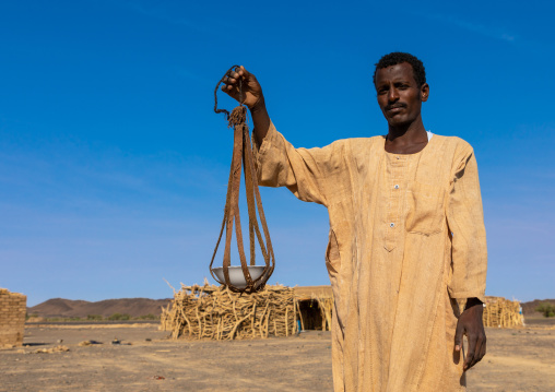 Bedouin arab man with a leather tool for kitchen, Northern State, Bayuda desert, Sudan