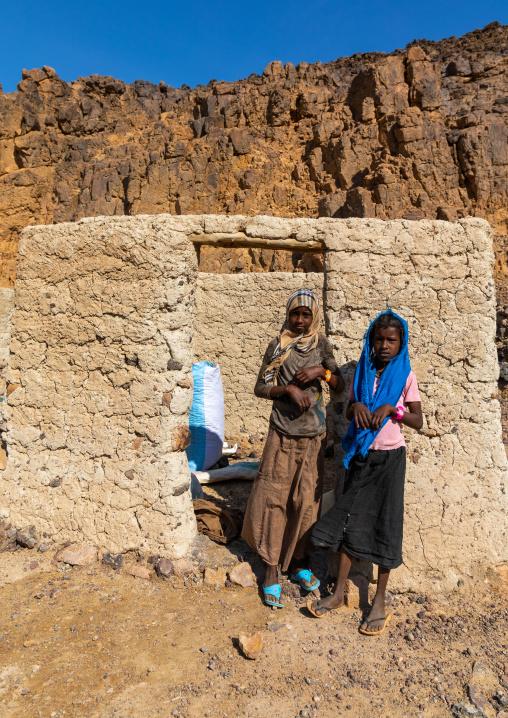 Bisharin nomad girls collecting salt in Atrun crater, Bayuda desert, Atrun, Sudan